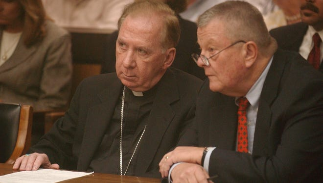 Bishop Thomas O'Brien (left), the former head of the Roman Catholic Diocese of Phoenix, and his attorney Tom Henze listen to Maricopa County Superior Court Judge Eddward Ballinger on July 7, 2003, during O'Brien's arraignment in a fatal hit-and-run.