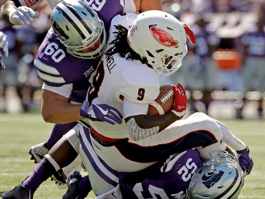 FILE - In this Sept. 17, 2016, file photo, Florida Atlantic running back Gregory Howell Jr. (9) is tackled by Kansas State linebacker Charmeachealle Moore (52) and defensive tackle Will Geary (60) during an NCAA college football game in Manhattan, Kan. Kansas State, with its rushing defense ranked third among FBS teams, faces Oklahoma this week. (AP Photo/Charlie Riedel, File)