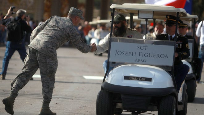 A service member from Goodfellow Air Force Base shakes the hand of combat veteran Army Sgt. Joseph Figueroa during a parade in honor of Figueroa and other veterans in 2015.