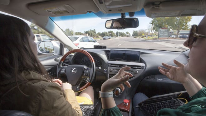 Driver Priscilla Knox and Jaime Waydo, a Waymo engineer, demonstrate a self-driving car.