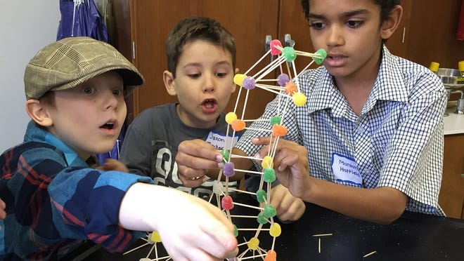 Fourth-graders Gibson Fansher, left, and Montana Hatfield, right, and second-grader Jaxon Thacker react as their gum drop and toothpick tower threatens to collapse.