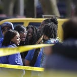 Bystanders and grieving friends of a victim quickly gather near an area secured by Milwaukee Police Department officers after a shooting left one person dead near N. 19th St. and Capitol Drive in April.