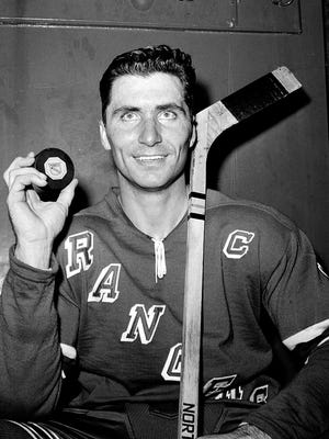 In this Nov. 12, 1961, file photo, New York Rangers forward Andy Bathgate poses in the locker room at New York's Madison Square Garden,  holding the puck that accounted for the 200th goal of his career, which he scored against the Chicago Blackhawks. Bathgate, a Hall of Fame winger and one of the most prolific scorers of his day, died the Hockey Hall of Fame and by the New York Rangers confirmed.