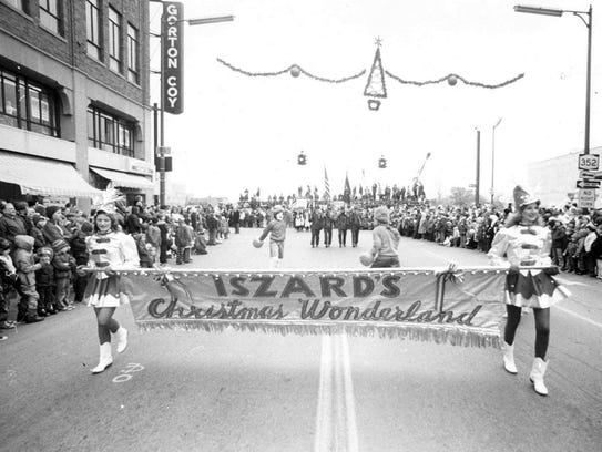 Majorettes carry an Iszard's banner down Main Street