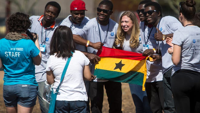 Chelsea Clinton poses with a group of refugees from Ghana during the Clinton Global Initiative University's Day of Action on Sunday at the PHX Renews lot in Phoenix. Chelsea and her father, Bill, volunteered at the lot.