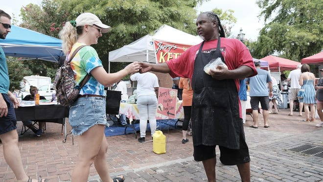 Megan Avery (left) takes a free sample of kettle corn from Jerry Johnson at the Augusta Market on the River before the pandemic. The Augusta Commission will consider reopening city venues to outdoor events at a Tuesday meeting.