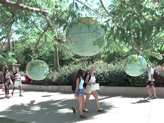 THEN: Plastic inflatable globes hang from trees on