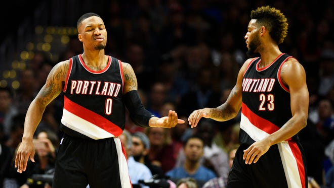 Portland Trail Blazers' Damian Lillard, left, celebrates with Allen Crabbe after he was fouled as he attempted a shot during the second quarter of an NBA preseason basketball game against the Los Angeles Clippers in Los Angeles, Thursday, Oct. 22, 2015.