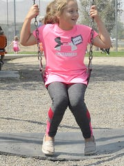 Third-grader Grace Chapin plays on the swings at Fernley