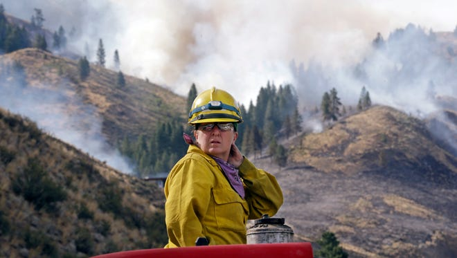 Firefighter Kathleen Calvin looks around as she sits atop her fire truck while waiting to begin work as smoke from a wildfire fills the sky behind Saturday, July 19, 2014, in Winthrop, Wash. A wind-driven, lightning-caused wildfire racing through rural north-central Washington destroyed about 100 homes Thursday and Friday.