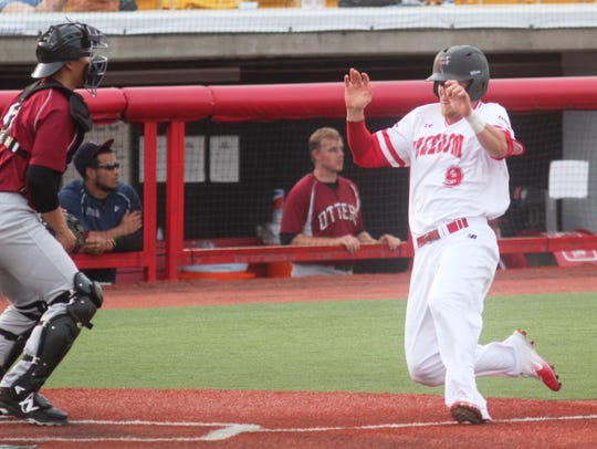 Collins Cuthrell slides into home plate for one of