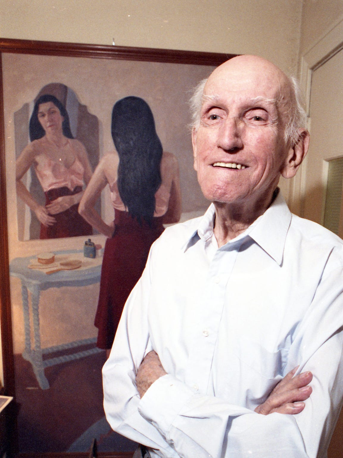 "Antonio E. Garcia stands before his 1933 painting ""Woman Before Mirror,"" for which his wife Herminia was the model, in April 1991."