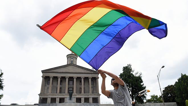 Christopher Shappley waves a gay pride flag during a celebration Friday at Legislative Plaza after the Supreme Court officially recognized the legal authority for same-sex couples to be married.