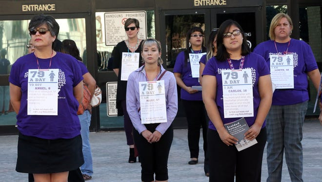 Employees and volunteers of the Center Against Sexual and Family Violence stand at the entrance to the El Paso County Courthouse with stories of some of the center's residents during a 79 A Day Rally Monday.