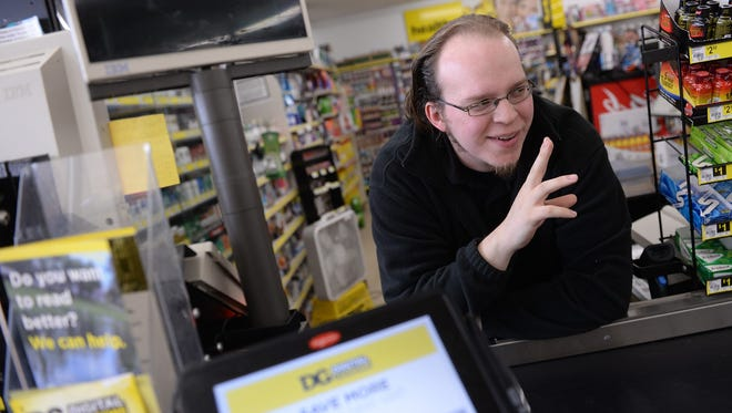Lucas Holliday waves to a customer while posing for a portrait at the Dollar General, 5640 S. Martin Luther King Blvd. in Lansing last November.