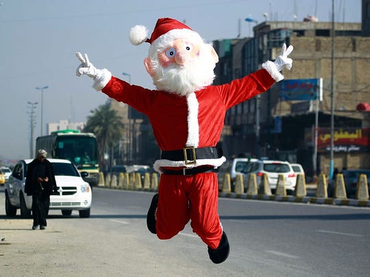 A man dressed in a Santa Claus outfit performs in the Shiite holy city of Najaf on Dec. 17, 2015.