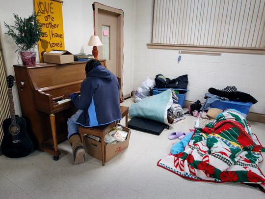 A resident plays the piano for the others at Tippecanoe