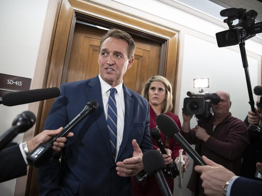 FILE- In this Dec. 6, 2018, file photo, Sen. Jeff Flake, R-Ariz., speaks with reporters on Capitol Hill in Washington. President Donald Trump's most prominent GOP critics on Capitol Hill are days away from completing their Senate careers, raising the question of who will take their place as willing to publicly criticize a president who remains popular with Republican voters. Sens. Jeff Flake of Arizona and Bob Corker of Tennessee engaged in a war of words with the president on myriad issues over the past 18 months, generating headlines and fiery tweets from a president who insists on getting the last word. (AP Photo/J. Scott Applewhite, File)