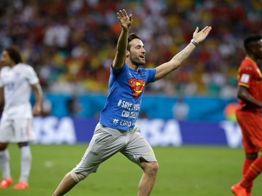 A man who ran onto the pitch gestures during the World Cup round of 16 soccer match between Belgium and the USA at the Arena Fonte Nova in Salvador, Brazil, Tuesday, July 1, 2014. (AP Photo/Matt Dunham)