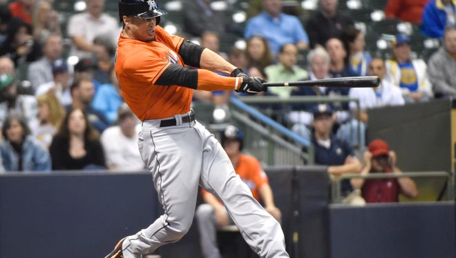 Marlins right fielder Giancarlo Stanton hits a solo home run against the Brewers on Sept. 8.
