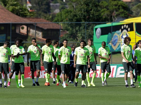 Brazilian players walk onto the pitch for a training session in Teresopolis, Brazil, Wednesday, June 25, 2014. Brazil will face Chile on June 28 in the round of 16 of the 2014 soccer World Cup. (AP Photo/Andre Penner)