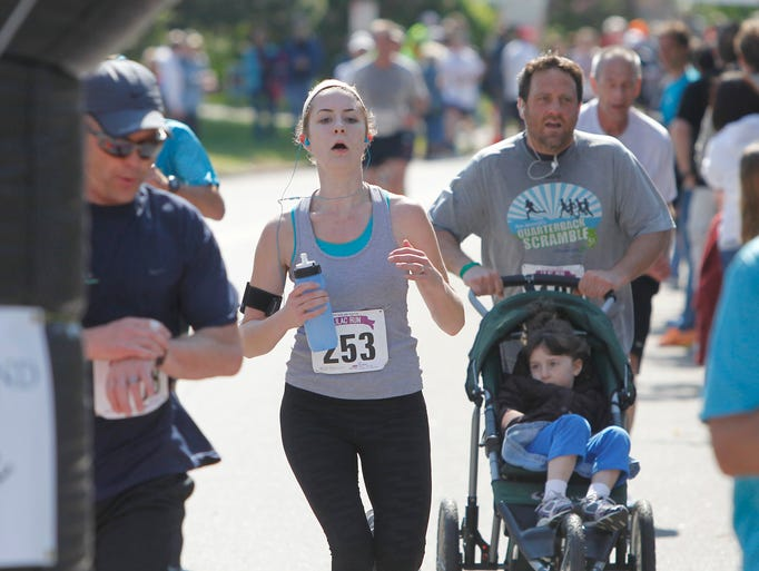 Runner approach the finish line of the Lilac 10K Race at Highland Park in Rochester Sunday morning, May 18, 2014.
