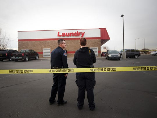 Farmington police officers confer at the scene of a stabbing Friday at the Laundratopia parking lot at 101 Gooding Lane in Farmington.