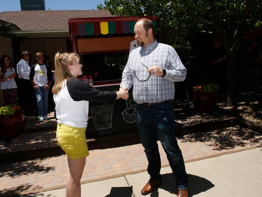 Keely Stockham shakes hands with Farmington Mayor Nate Duckett Tuesday at Keely's Lemonade Stand on North Orchard Avenue in Farmington.