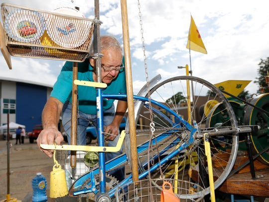 Tom Gifford sets up an antique engine Thursda during Bloomfield's Party in the Park at Bloomfield High School.