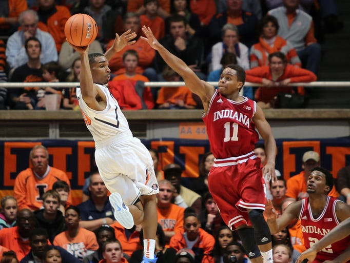 Dec 31, 2013; Champaign, IL, USA; Illinois Fighting Illini guard Tracy Abrams (13) passes the ball while guarded by Indiana Hoosiers guard Kevin Ferrell (11) at State Farm Center. Mandatory Credit: Ben Woloszyn-USA TODAY Sports