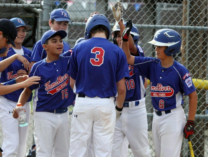 Little League Section 3 tournament game between Toms River and Manalapan at Sayreville Little League field in Sayreville.  Toms River's # 3 (center)-Jonathan Giordano is congratulated by team mates at home plate after hitting a two run home run in early inning play at Sayreville.     On Wednesday July 16,2014 Photo: Mark R. Sullivan/Staff Photographer