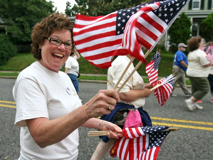 Cecilia Covino with the Tricentennial Committee, hands out flags to parade goers, during the Lebanon Borough Fourth of July Parade, July 04 2014. Lebanon NJ. photo by Kathy Johnson BRI 0704 Fourth of July, Lebanon Borough