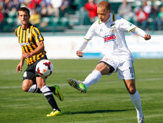 Rochester's J.C. Banks, right, looks to send a ball down field past Charleston's Jarad Van Shaik during their home opener of USL soccer action between the Charleston Battery and the Rochester Rhinos at Sahlen's Stadium in Rochester Sunday evening, April 27, 2014.