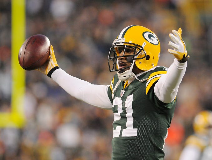 Charles Woodson motions to the crowd after his interception