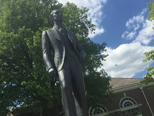 A Henry Ford statue stands in front of the Ford museum.
