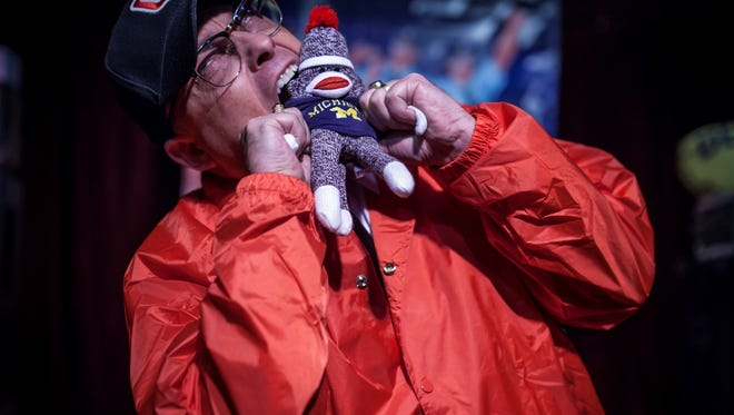 Bo Biafra, lead singer for the punk-rock band the Dead Schembechlers, takes a bite out of a Michigan-clad doll during a performance in recent years.
