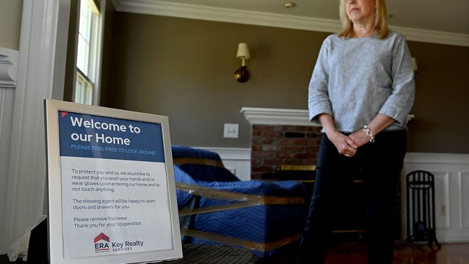 Real estate agent Denise Archer with her sign asking prospective buyers to wash their hands and/or wear gloves and to not touch anything while looking at a property at 20 Butler Road in Mendon.