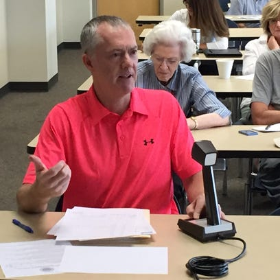 Insurance Commissioner Nick Gerhart responds to frustrated health-insurance consumers during a hearing Saturday.