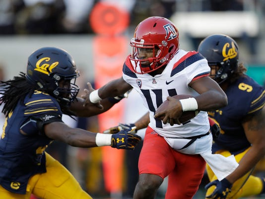 FILE - In this Saturday, Oct. 21, 2017, file photo, Arizona quarterback Khalil Tate, center, runs for a touchdown past California linebacker Alex Funches, left, during the first half of an NCAA college football game in Berkeley, Calif. Arizona's quarterback situation was resolved three games ago when Tate took over as starter. Other Pac-12 teams haven't had the same success in navigating mid-season QB quandaries. Injuries have impacted Oregon and Oregon State at the position.  (AP Photo/Marcio Jose Sanchez, File)