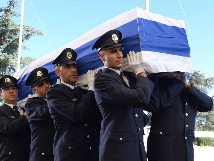 Members of a Knesset guard carry the flag-draped coffin