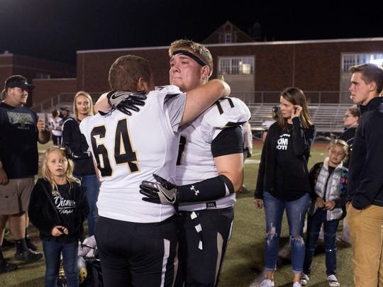 Boonville's Payton Ayscue (64) and Eli Franz (77) embrace after their 20-14 sectionals loss to Bosse High School at Enlow Field in Evansville, Ind., on Friday, Oct. 20, 2017.