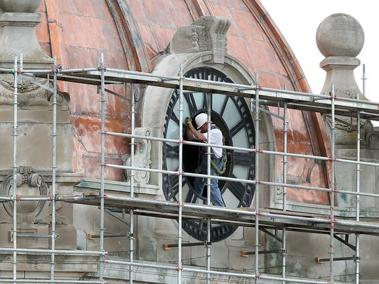 A worker talks through the face of a clock atop the Brown County Courthouse in the spring of 2017. Repair work restored the Green Bay building's copper dome to its original sheen, but six months after the work ended, the dome again looks similar to the wqay it did before repairs began.