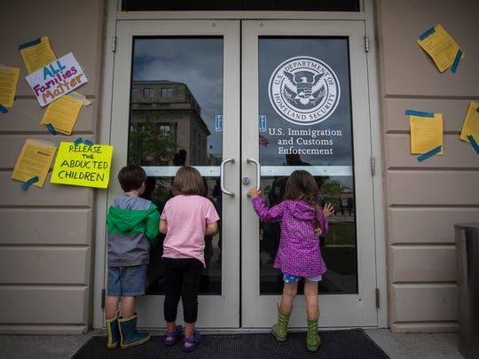 Children look inside the doors at the U.S. Immigration and Custom Enforcement office in downtown Louisville on Thursday. Over 200 attended a protest regarding ICE and the separation of immigrant families. June 21, 2018