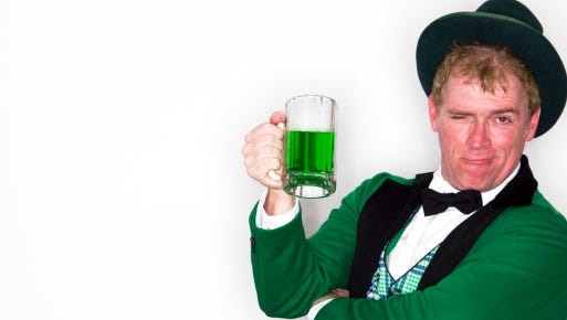 Man dressed as Leprechaun with mug of green beer