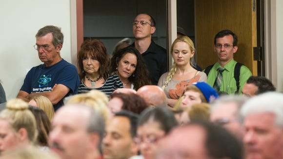People stand in the doorway during a Gilbert school board meeting Tuesday, March 25, 2014.