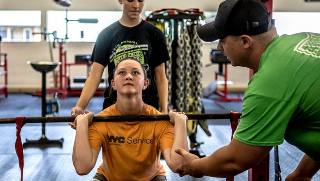 Nick Showman helps Emma McCracken of Newark Catholic with proper form while Alyssa Back of Newark spots for her. The girls are participating in a specially designed strength training program for softball players.