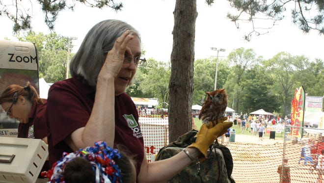 Nancy Vitrius, 70, of Binghamton, shows of Spec, a rescued Screech Owl, as part of the Ross Park Zoo's ZooMobile at the July 4th Extravaganza at Highland Park on Tuesday.