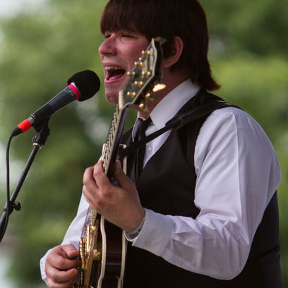 Robert Murray as George Harrison, performs with his