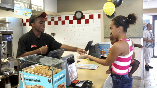 Crew member Quinton Fleming gives Destini Griffin, 15, holding cousin Ke'Marius Powell, 1, her change after the pair ordered a late lunch Friday. The McDonald's at 3645 Cleveland Ave. will be torn down and a new one built in its place.