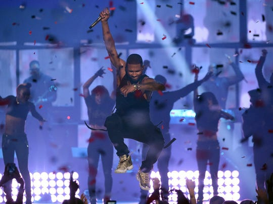 Usher jumps as he performs onstage during the 2014